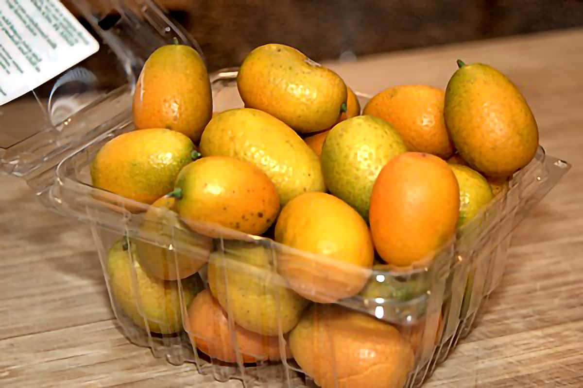 A plastic container of fresh kumquats.