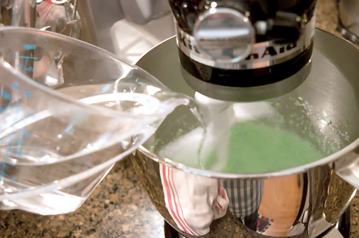 Boiling water being poured into the cream cheese and jello mixture in mixing bowl.