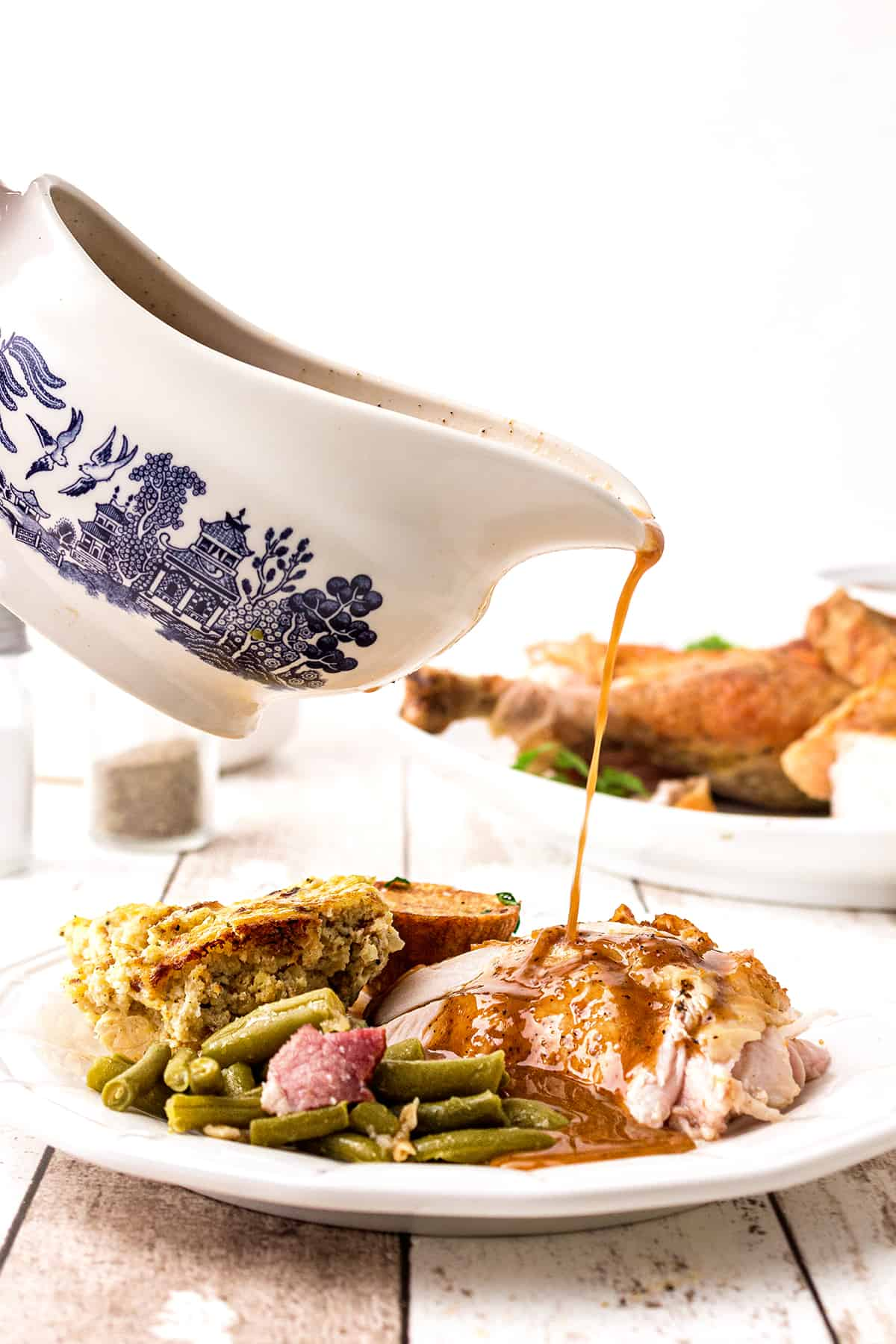 Gravy poured from a gravy boat onto a plate containing sliced oven roasted turkey and side dishes.