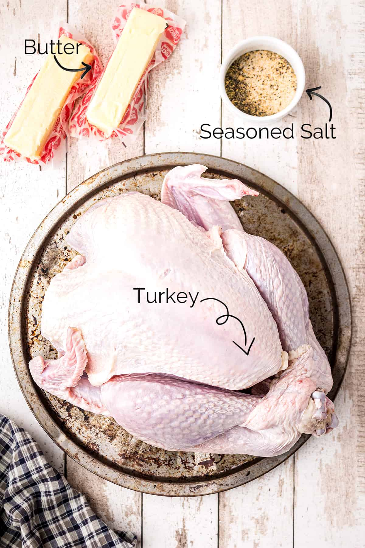 Ingredients of butter, seasoned salt, and turkey on a tray.