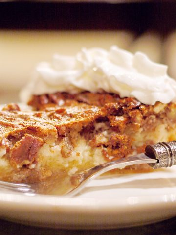 A slice of Pecan Cheesecake Pie on a serving plate with a fork alongside.
