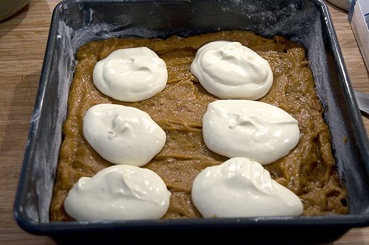The pumpkin batter in a baking pan with dollops of cream cheese batter on top.
