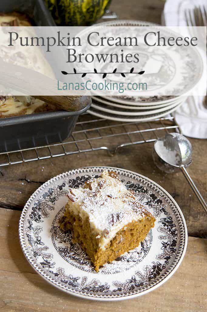 A serving of Pumpkin Cream Cheese Brownies on a plate dusted with powdered sugar. Text overlay for pinning.