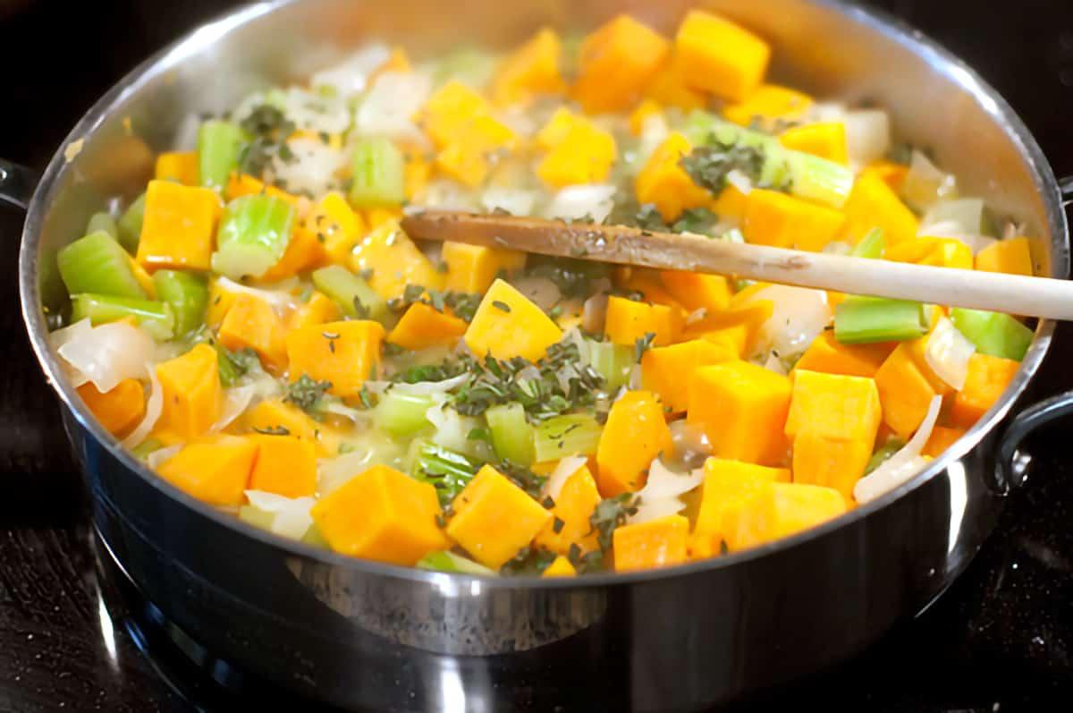 Vegetables cooking in a large skillet.