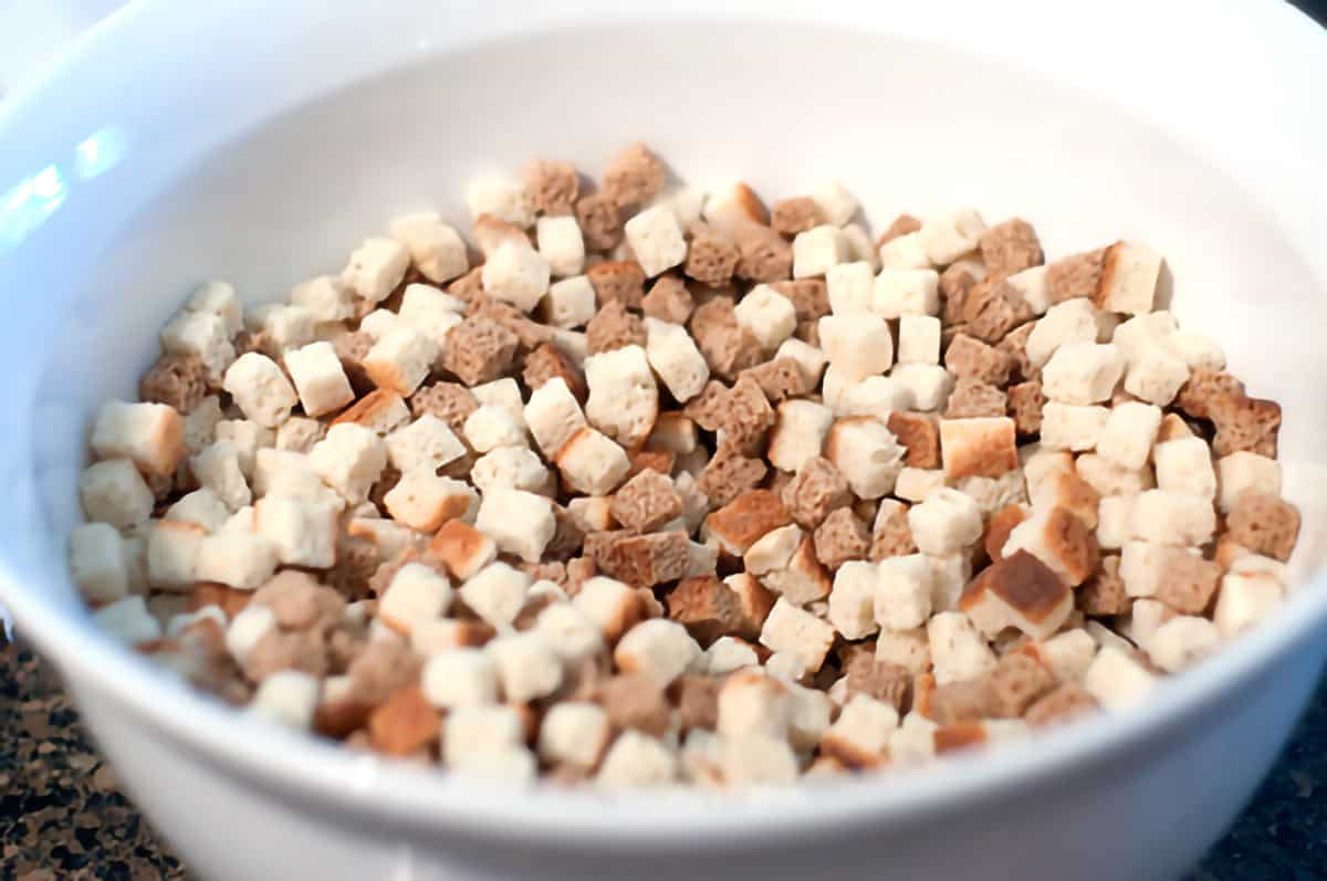 Large mixing bowl containing white and wheat bread cubes.