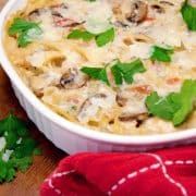 Classic Turkey Tetrazzini in a casserole baking dish with a red kitchen towel in the foreground.