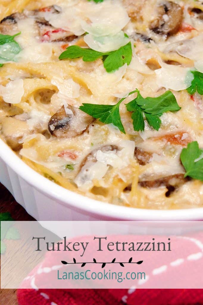 Classic Turkey Tetrazzini in a casserole baking dish with a red kitchen towel in the foreground. Text overlay for pinning.