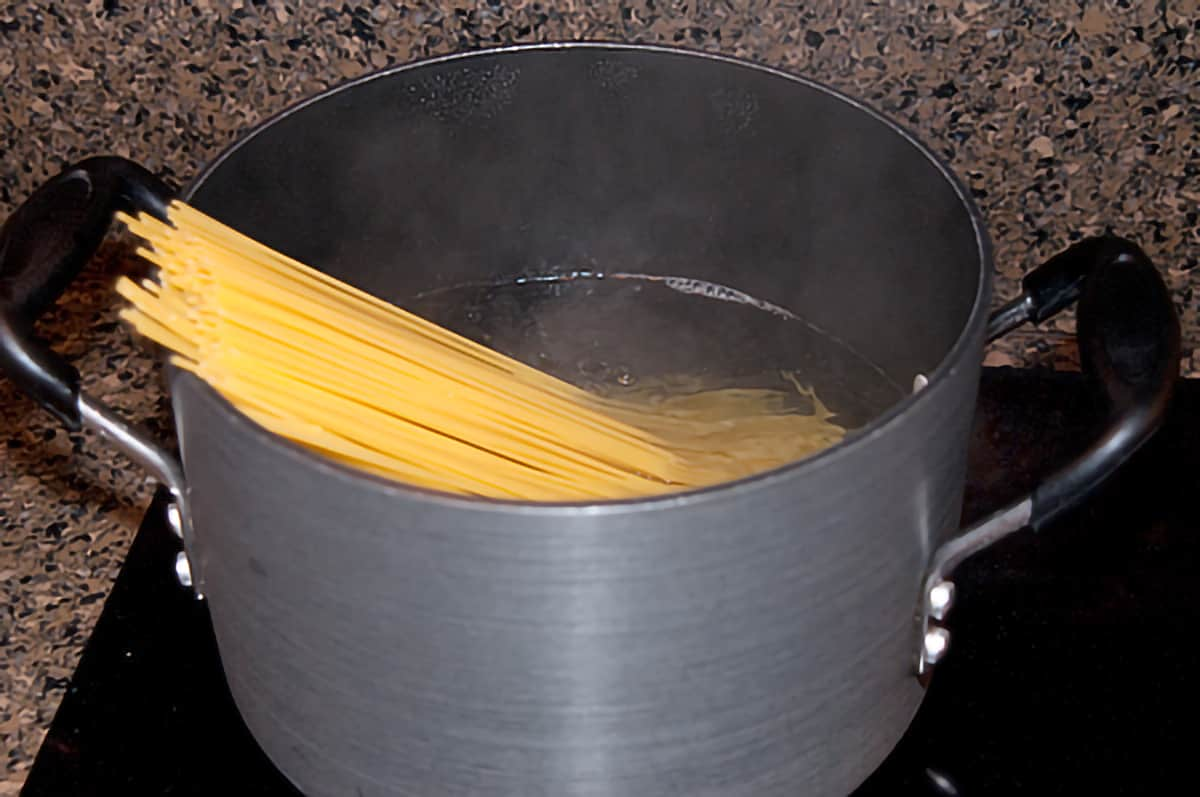 Spaghetti in a large pot on the stovetop.