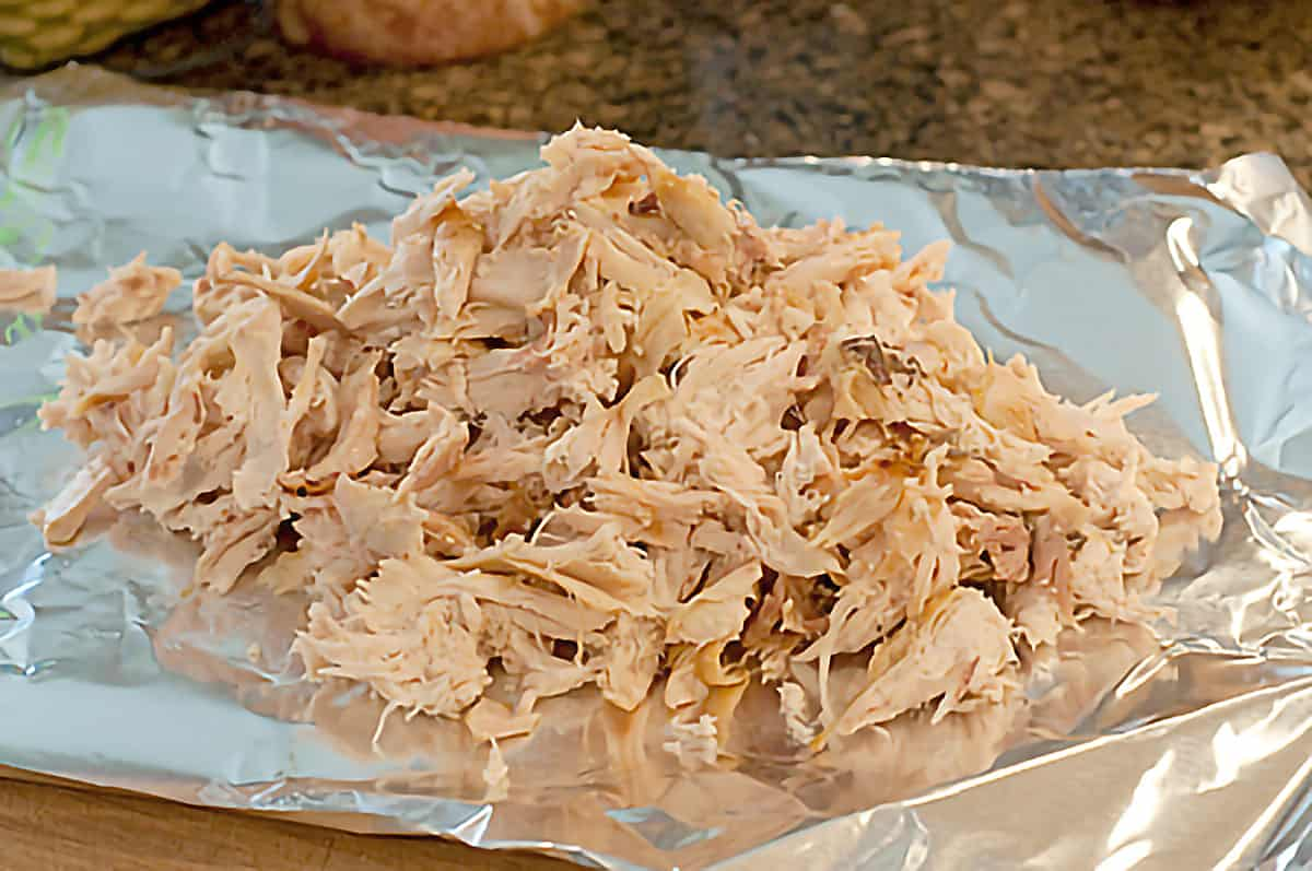 Shredded chicken on a large square of aluminum foil