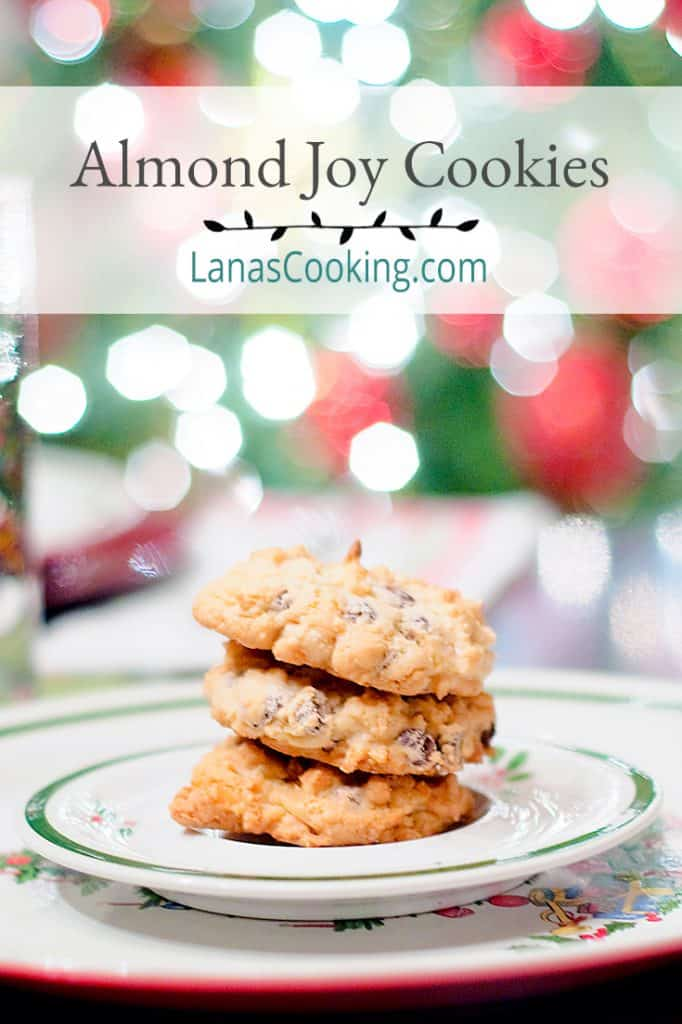 Almond Joy Cookies on a Christmas plate with twinkling lights in the background. Text overlay for pinning.