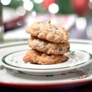 Almond Joy Cookies on a Christmas plate with twinkling lights in the background.