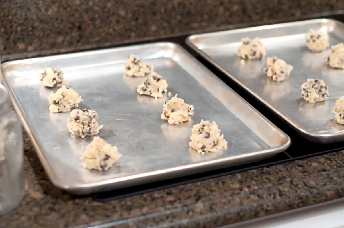 Two cookie sheets with portions of cookie mixture placed on them.