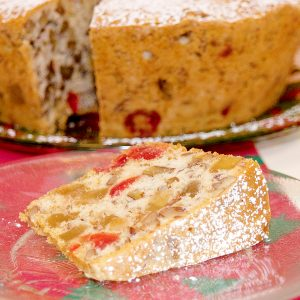 A slice of candied holiday fruitcake on a plate with remaining cake in background.