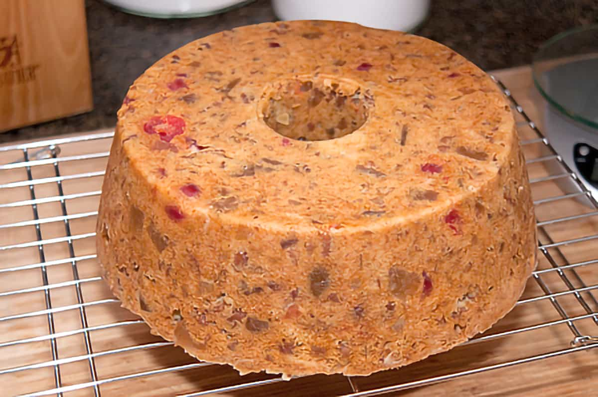 Baked fruitcake removed from the pan sitting on a rack to cool.
