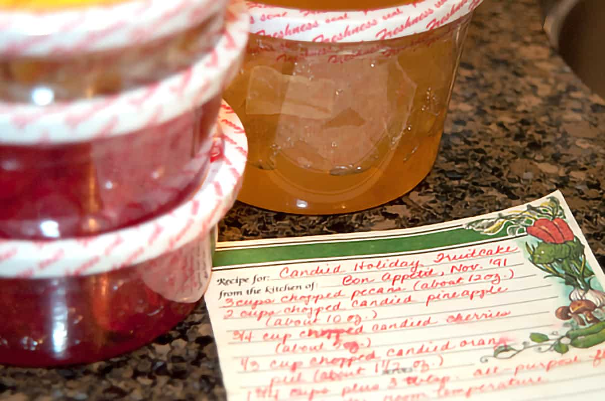 Handwritten recipe card in the foreground with candied fruit in the background.