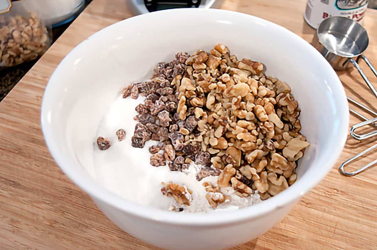 Mixing bowl containing flour, sugar, baking powder, dates, salt, and nuts for the recipe.