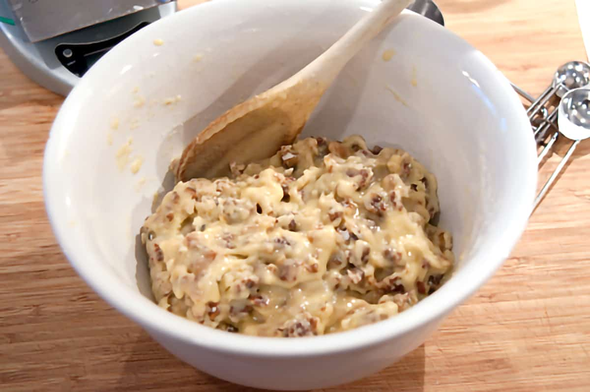 Flour, sugar, baking powder, dates, salt, and nuts with eggs added and stirred into the mixture.