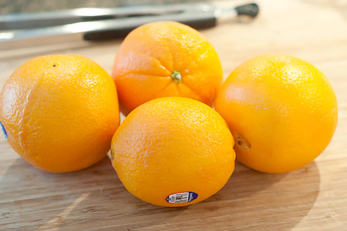 Four navel oranges on a cutting board.