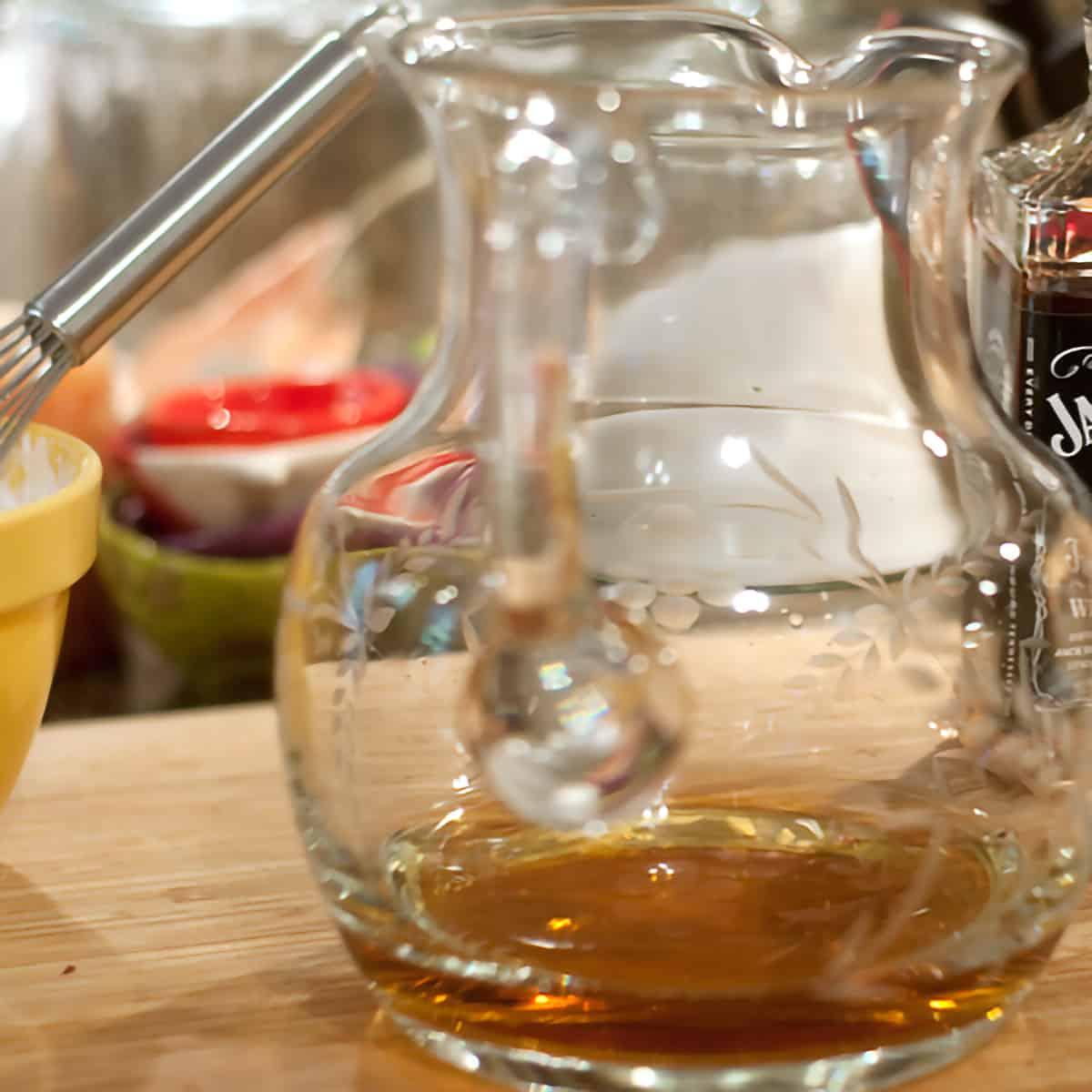 Glass pitcher containing bourbon.