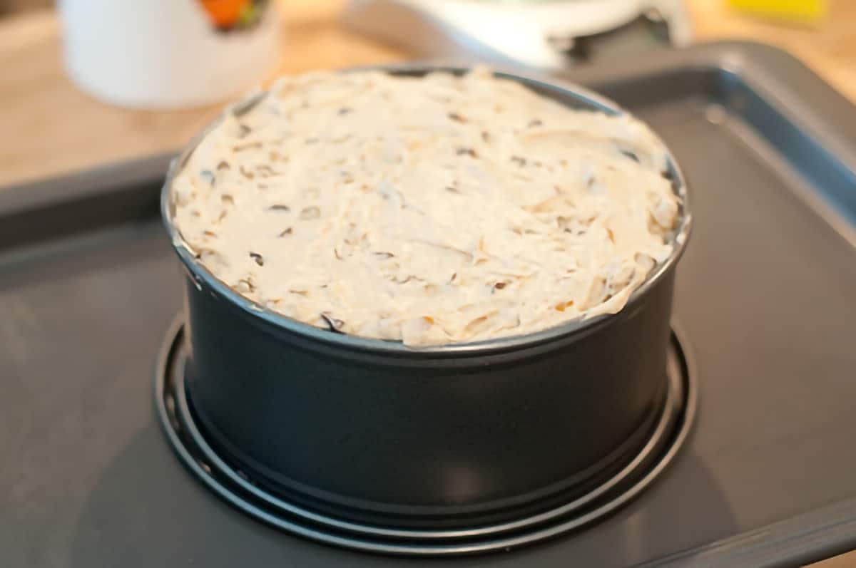 Cake batter in a pan set on a baking sheet.