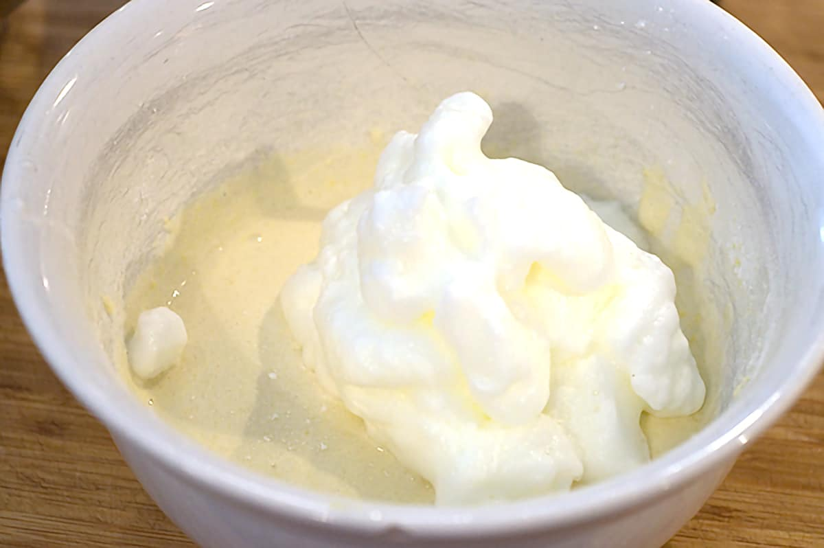 Beaten egg whites being folded into mixture in white mixing bowl.