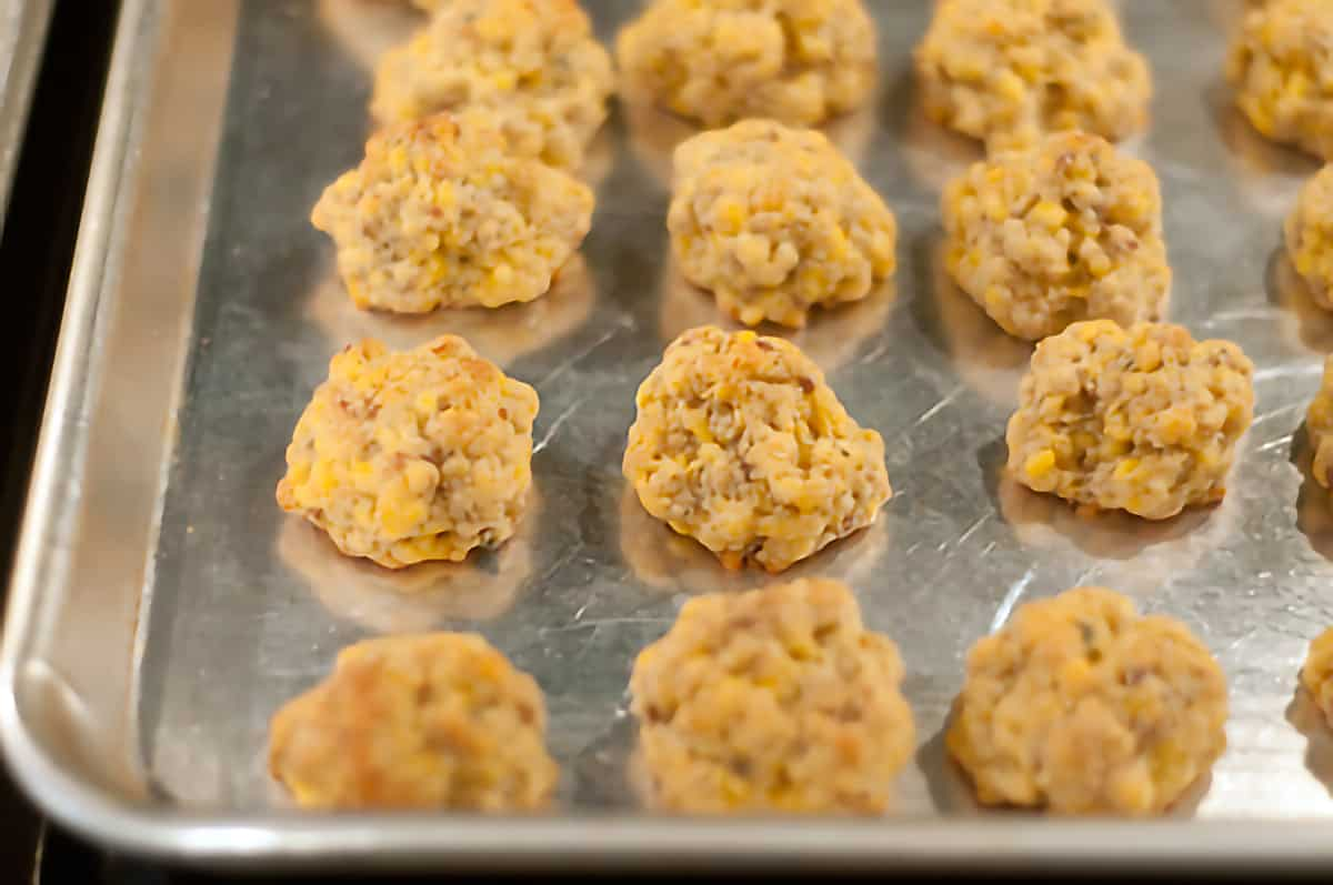 Finished sausage balls cooling on the baking sheet.