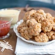 Sausage balls on a serving plate with two dipping sauces on bowls to the side.