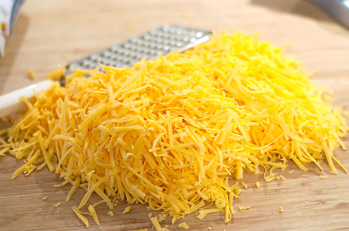 A mound of grated cheese along with a cheese grater on a cutting board.
