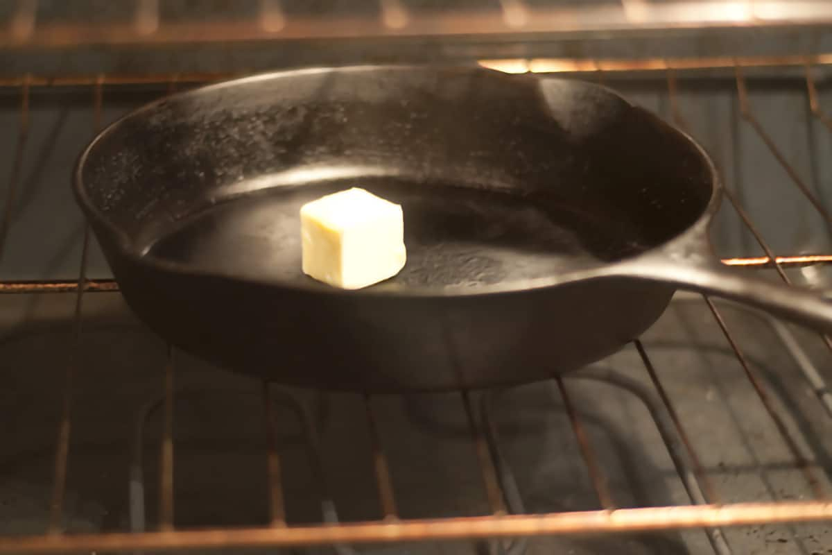 Cast iron skillet with butter on an oven rack.