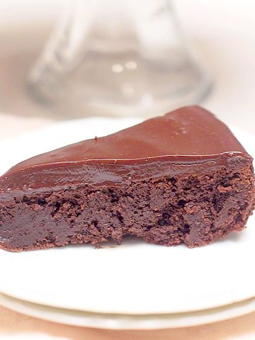 A slice of flourless chocolate cake with chocolate ganache on a serving plate.