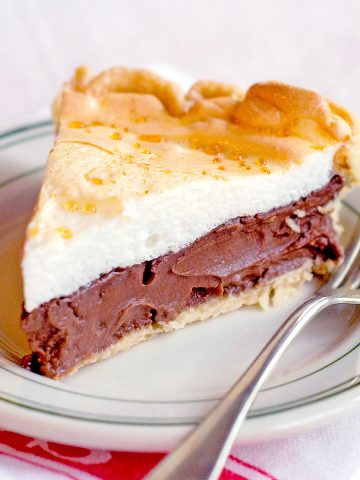 Slice of chocolate meringue pie on a white plate with a fork alongside.