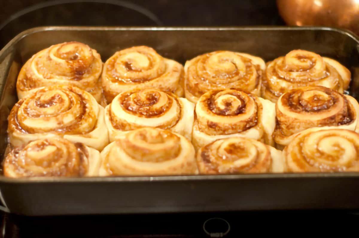 Baking pan with twelve baked cinnamon rolls.