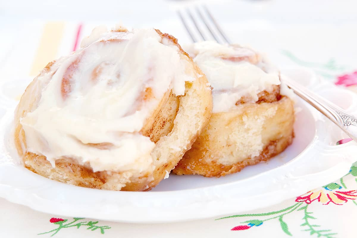Two cinnamon rolls with cream cheese icing on a white plate with a fork on the side.