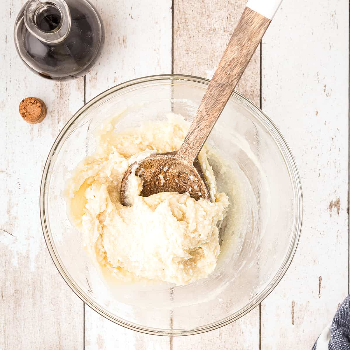 Medium bowl containing softened cream cheese, sugar, and vanilla stirred with wooden spoon