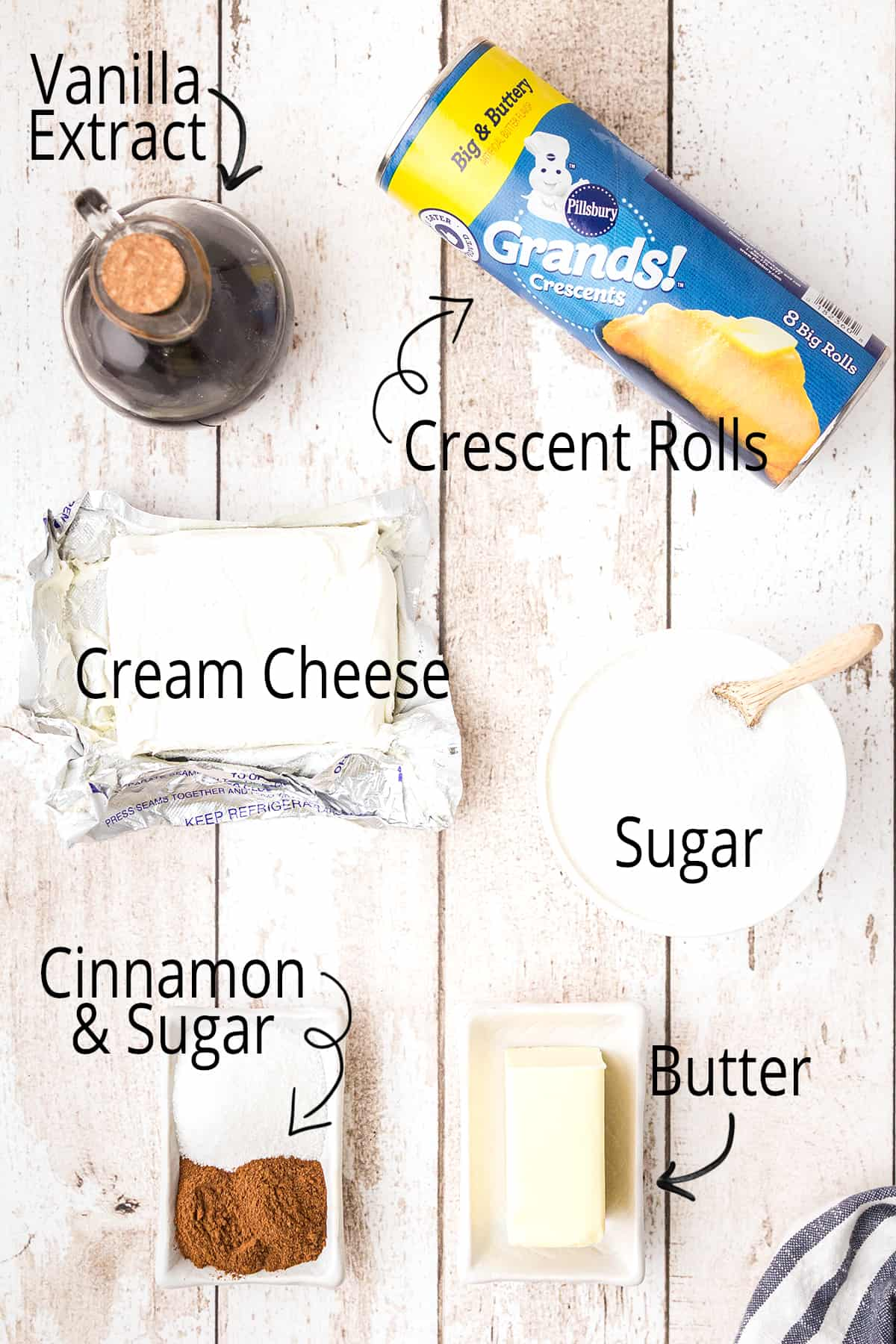 Ingredients needed for the recipe from left to right: vanilla extract, refrigerated crescent rolls, cream cheese, sugar, cinnamon-sugar mixture, and butter