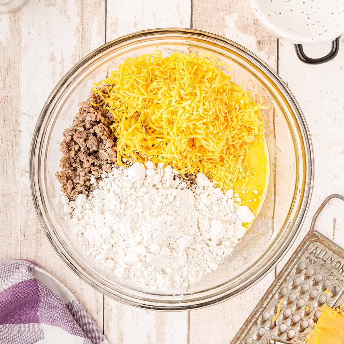Mixing bowl containing sausage, cheese, eggs, and baking mix