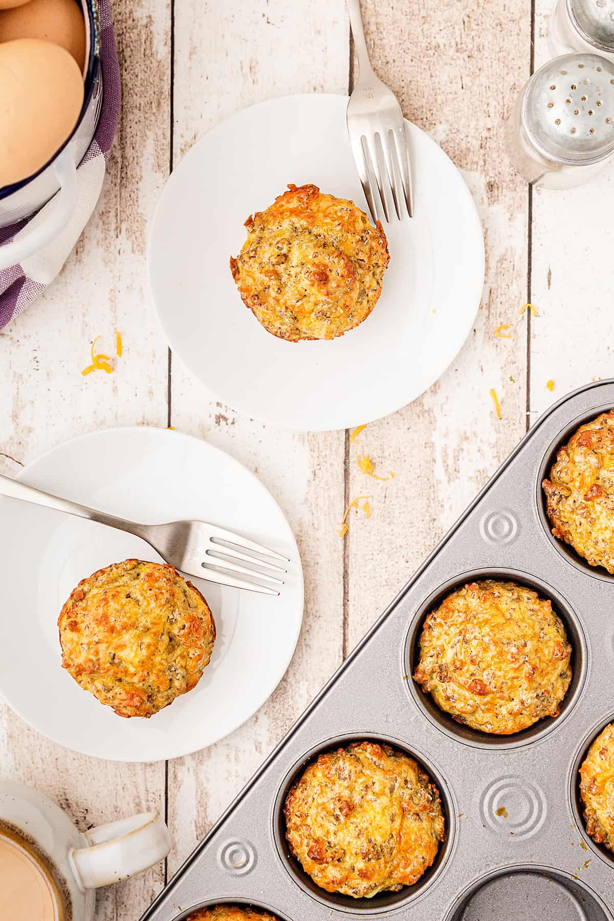 Easy Sausage Muffins on individual serving plates with baking tin in the foreground.