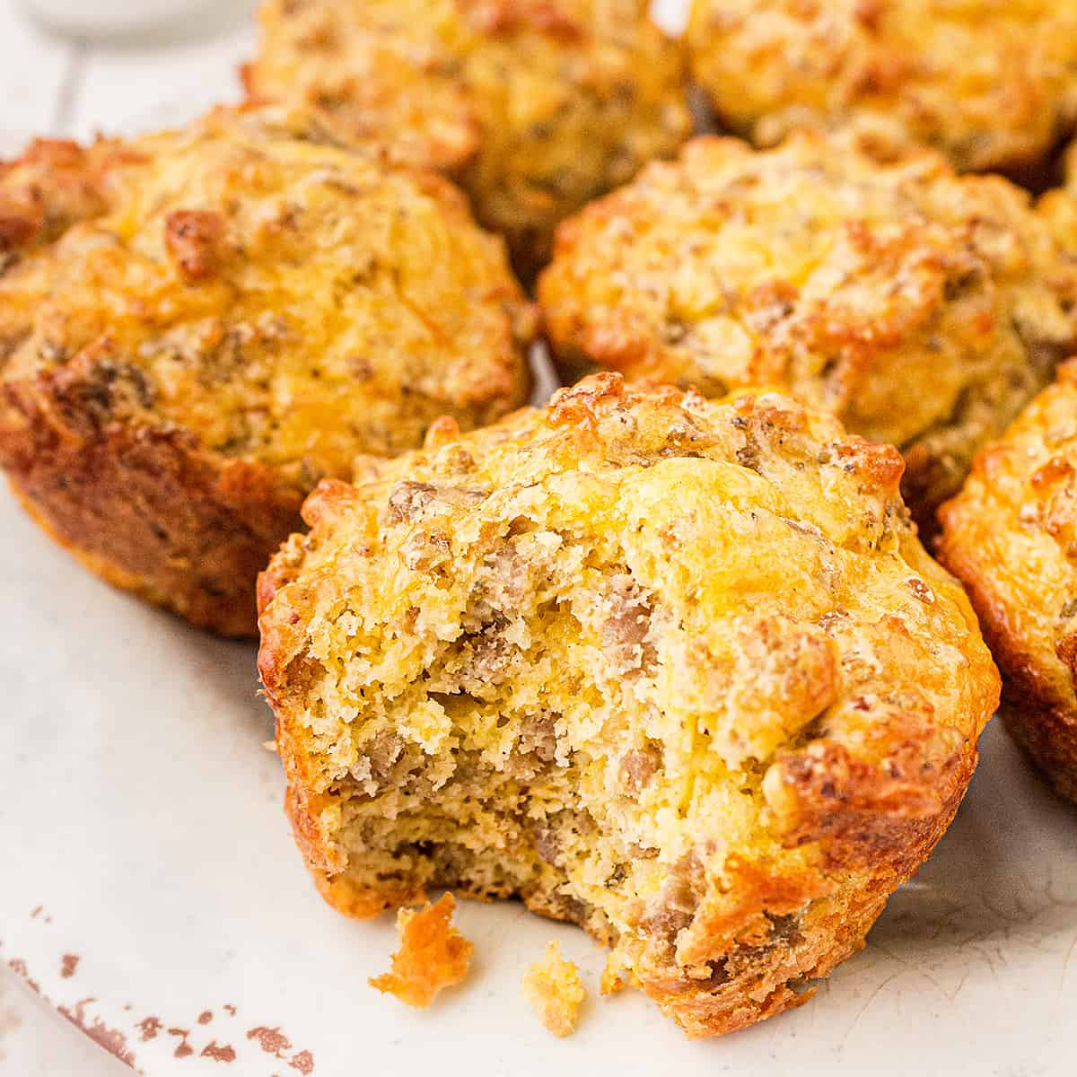 Easy Sausage Muffins on a serving plate; one muffins with a bite taken.