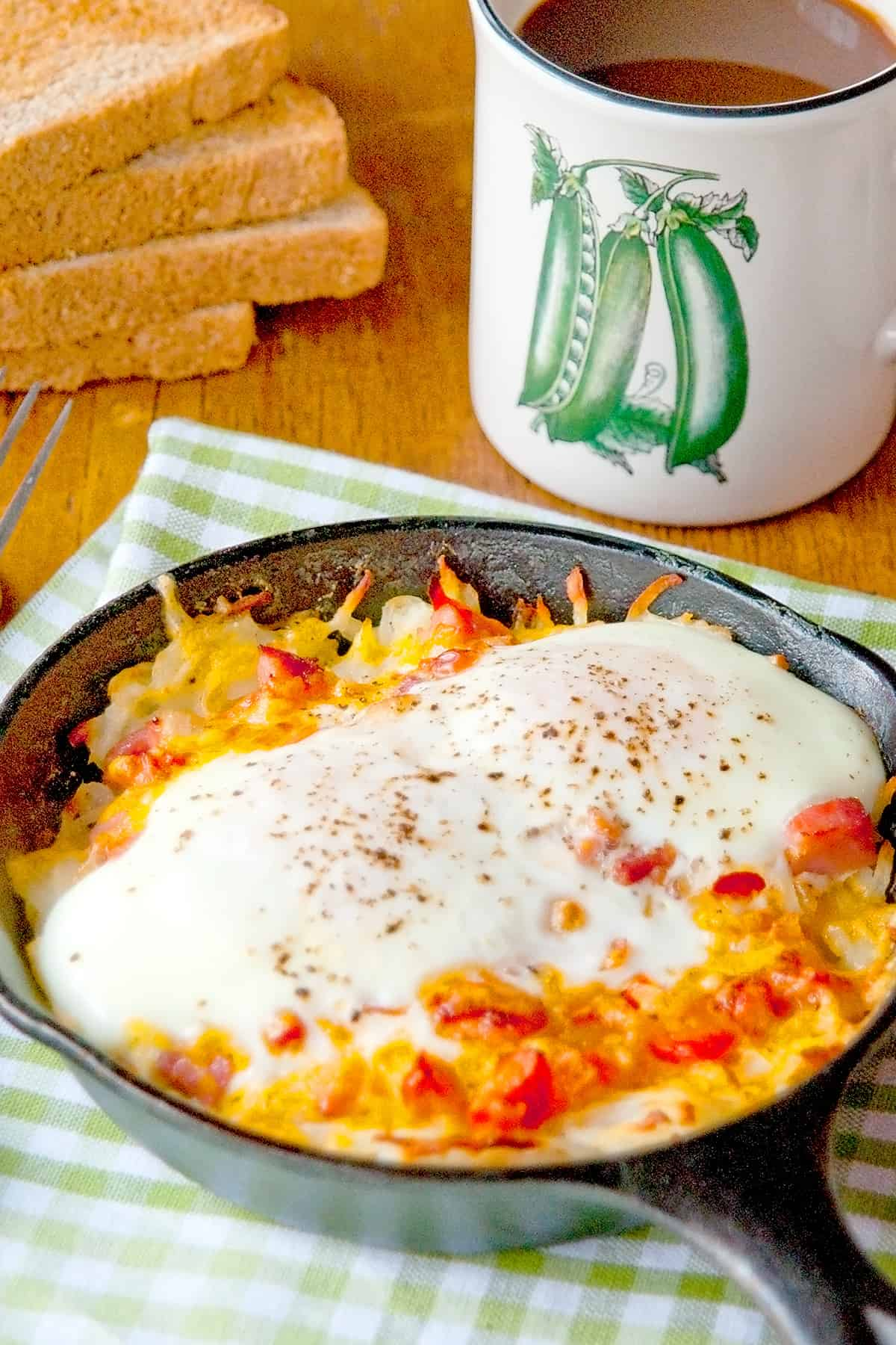 Hash Brown Breakfast Skillet on a kitchen towel with a cup of coffee in the background.