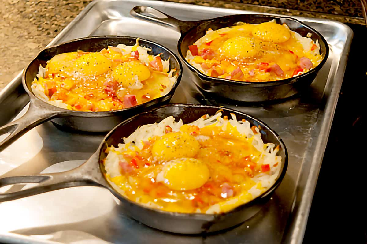 Skillets with eggs added to top of filling mixture.