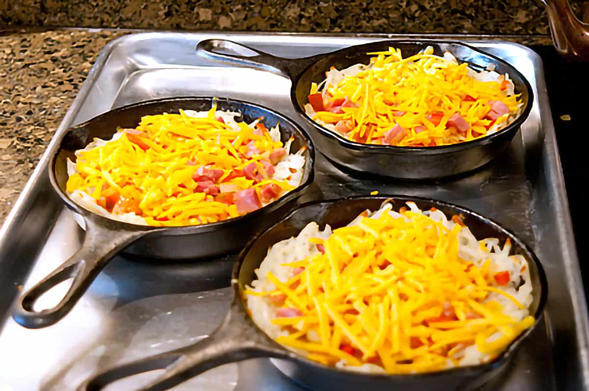 Skillets with filling and cheese added.