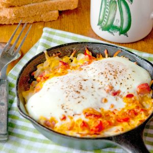 Hash Brown Breakfast Skillets on a kitchen towel with a cup of coffee in the background.