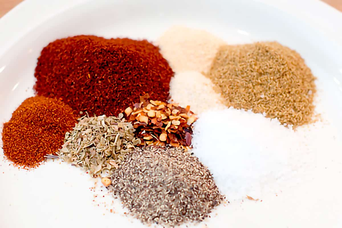 Herbs and spices for the seasoning mix measured out on a small plate.