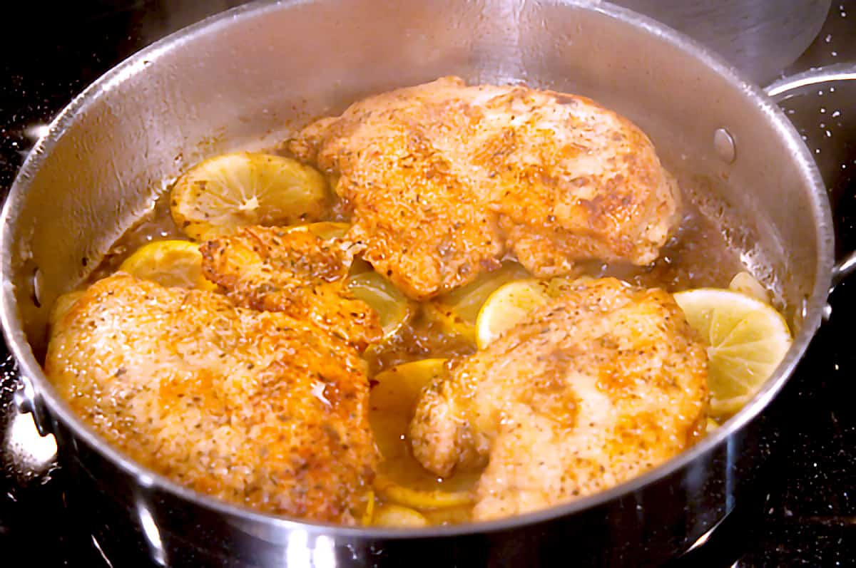 Pan fried chicken and lemon slices in a skillet.