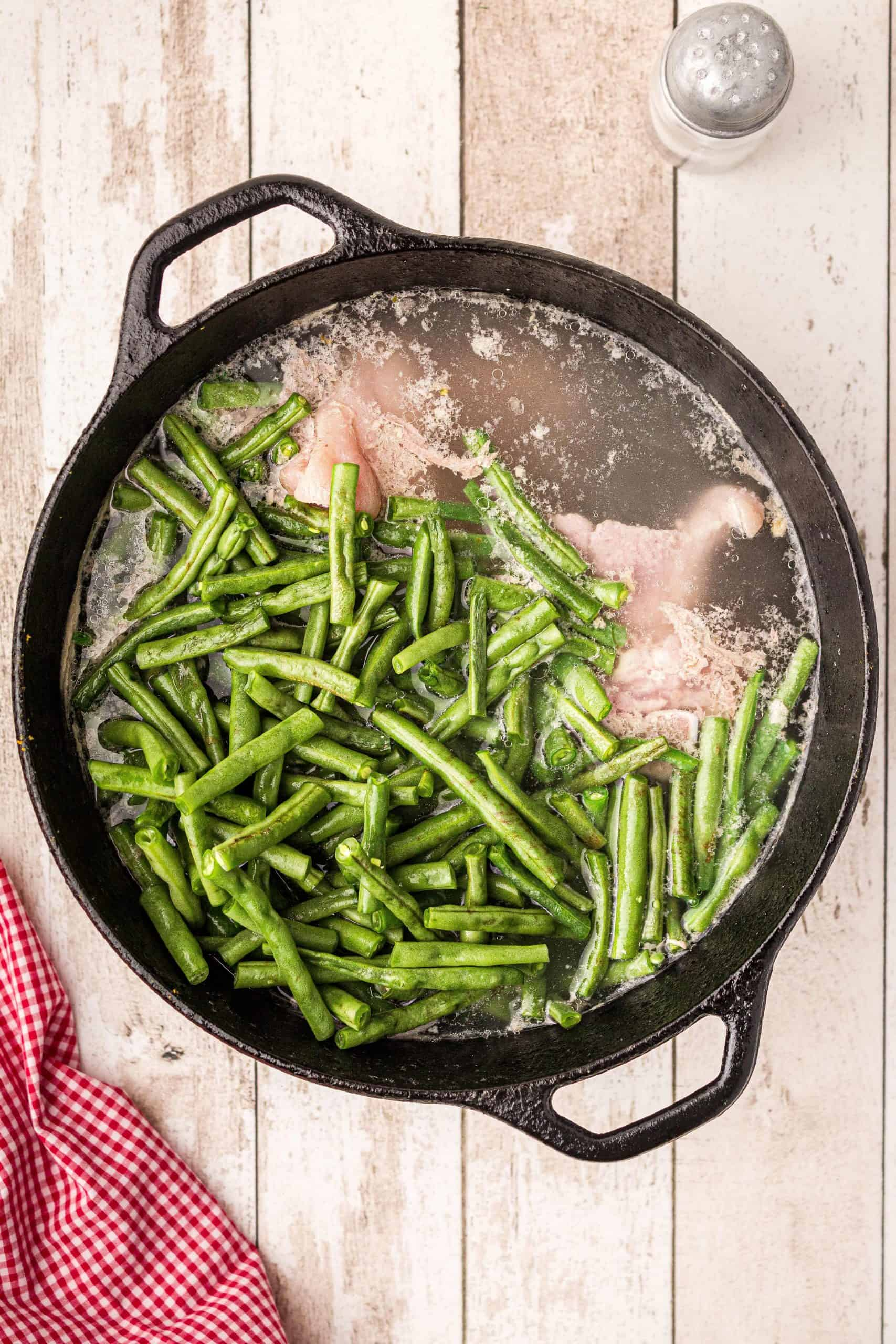 Cast iron cooking pot with ham hock broth and fresh green beans added.