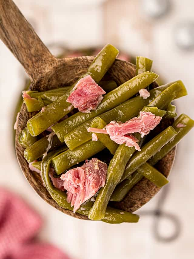 Wooden spoon filled with cooked southern style green beans and ham hock