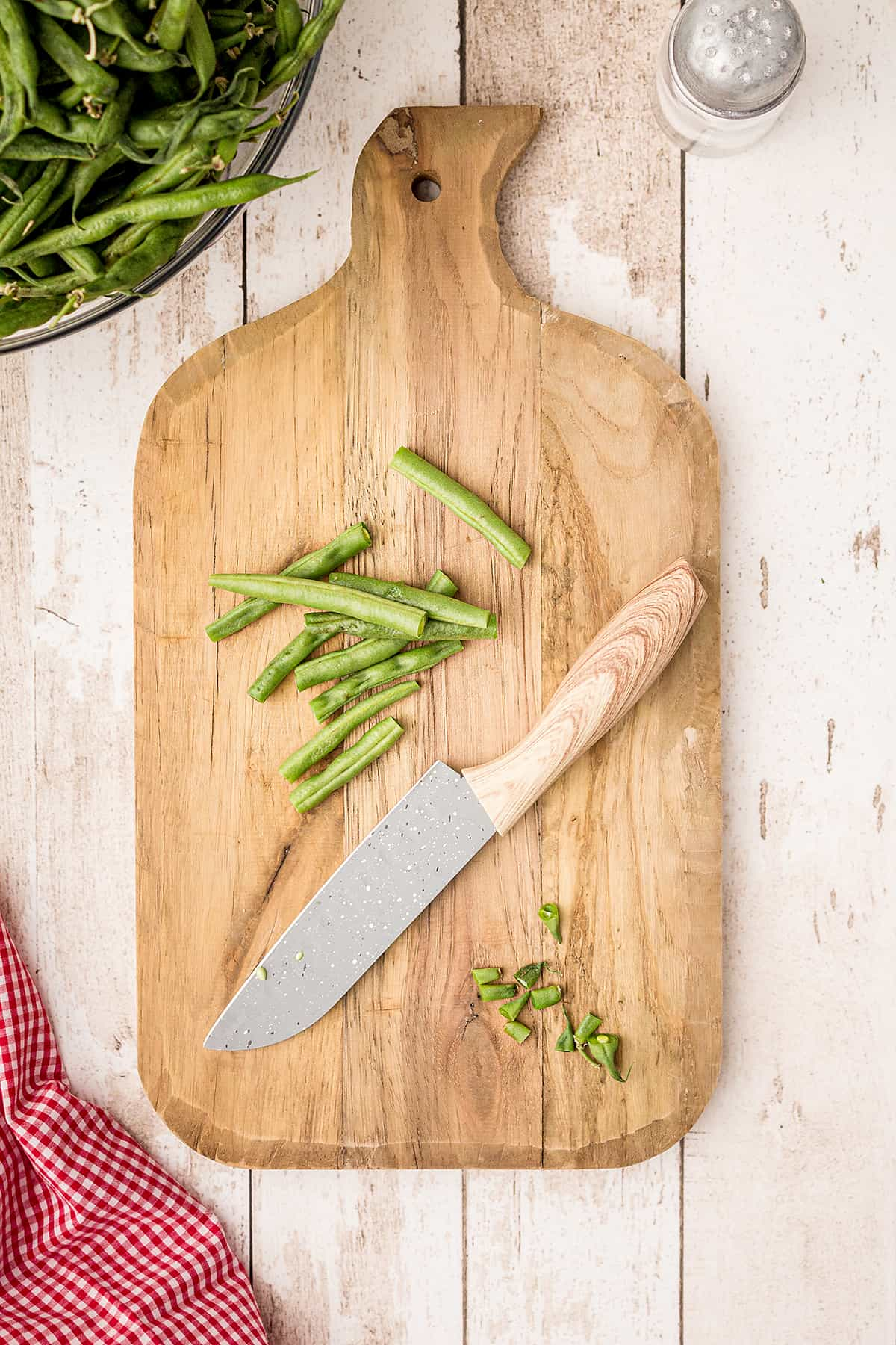 Fresh green beans on a cutting board with a knife.