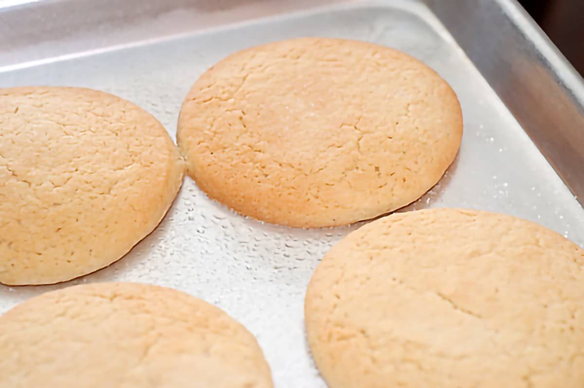 Cooked tea cakes on a baking sheet.