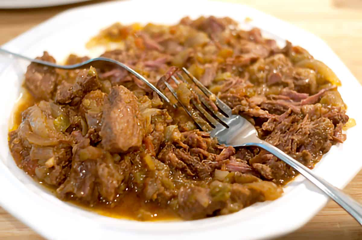Cooked beef on a plate with two forks.