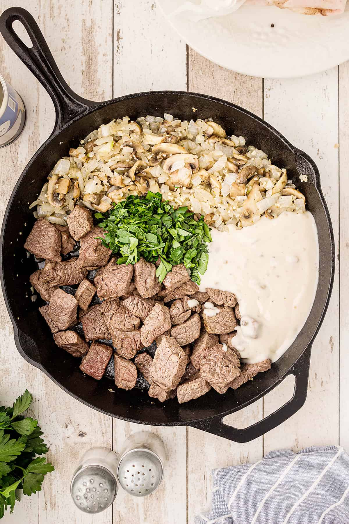 Cooked beef, vegetables, soup, and parsley added to cast iron skillet